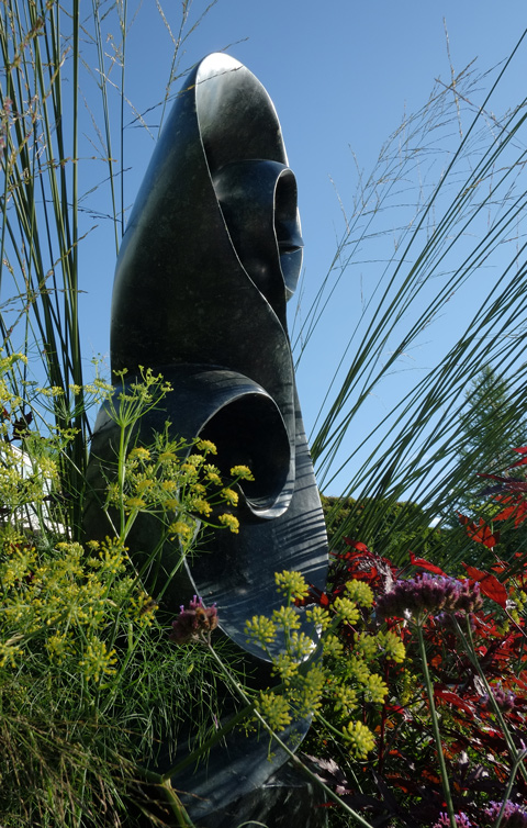 tall stone sculpture among plants in a garden