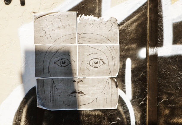 a hand drawn picture of a face, on paper, pasted on a fence