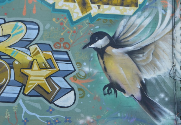 part of a mural, a bird coming into land, wings back, feet forward, body almost upright