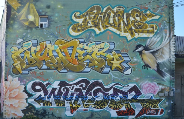 a wall with three large text throw-ups that all say Wunder, as a tribute to Mike Kennedy. Also a bird and a flower, a yellow star