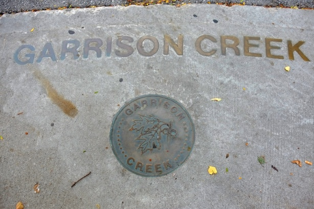 brass letters embedded in the sidewalk that say Garrison Creek, also a round metal medallion with the same words