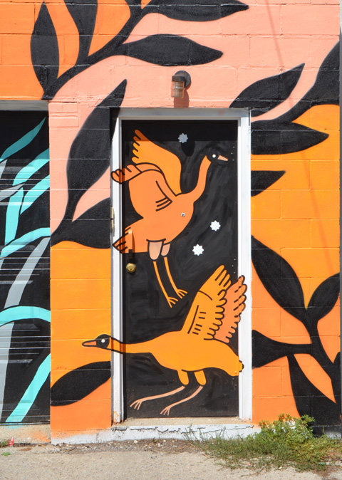 part of a mural, two orange geese on a door, black and orange, alley