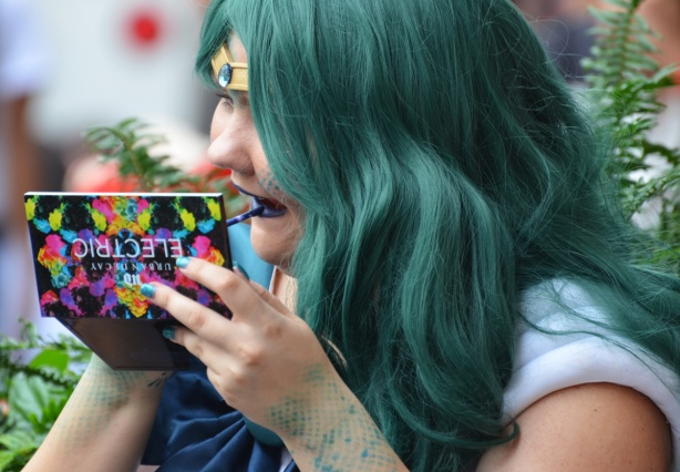 woman with green hair is applying blue lipstick