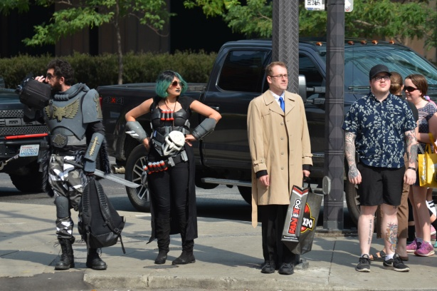 a group of people waiting for a green light, two are in costumes for Fan Expo