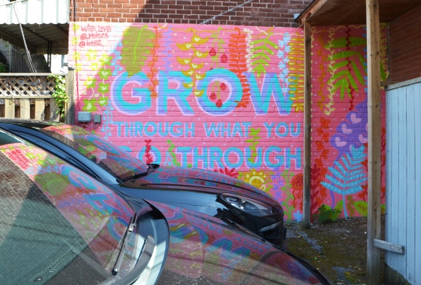 mural in pink and pale blue, with some greenand yellow flowers. Large words that say Grow through what you go through.