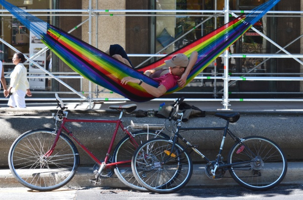 a young couple share a hammock strung between two trees on a diving strip own the middle of Yonge Street, their bikes are parked beside the hammock