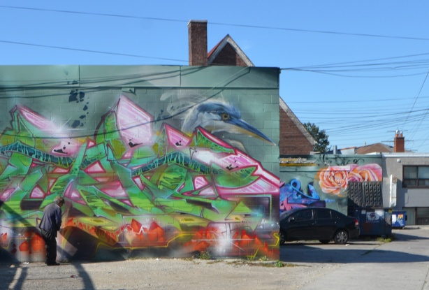 large mural in an alley, the head of a blue heron appears above abstract painting and text street art