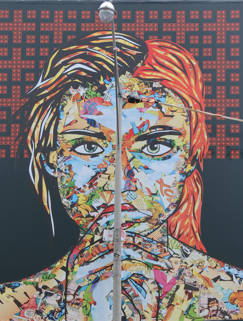 large maural by Daniel Mazzone, on construction hoardings, a woman's face and head, created by a collage of smaller images