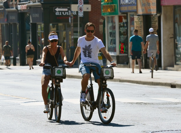 a couple cycles together up Yonge street, on rented Bixi bikes, holding hands