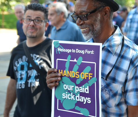 labour Day parade on Queen St West, an older black man carries a sign that says Hands Off our paid sick days