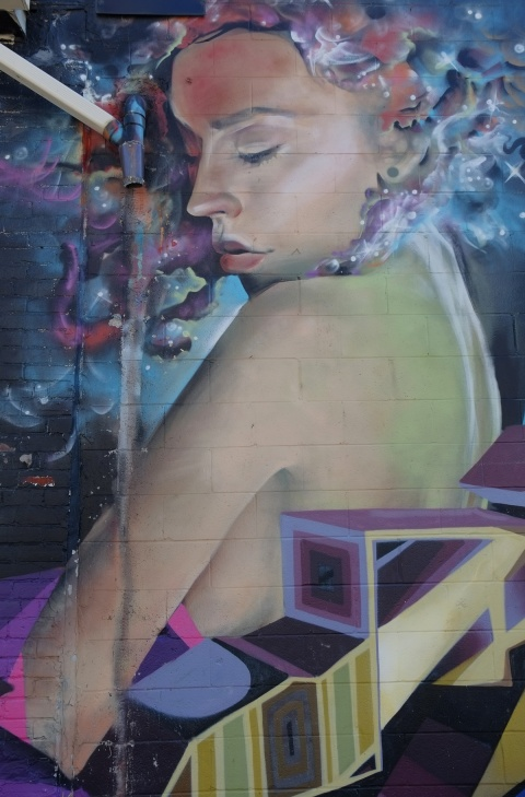mural by jarus in an alley, a woman looking over her shoulder