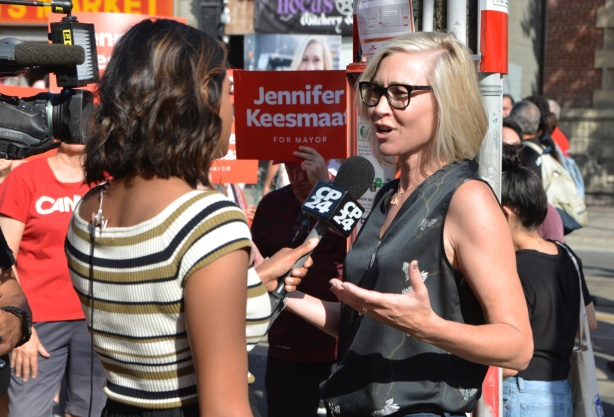 labour Day parade on Queen St West, mayoral candidate Jennifer Keesmaat being interviewed by a woman reporter from CP24 news, in the midst of the parade