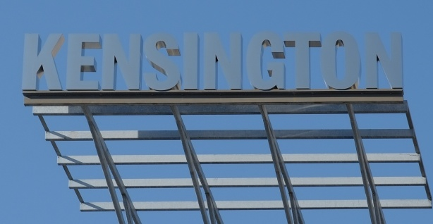 metal sign above the buildings, says Kensington in capital letters