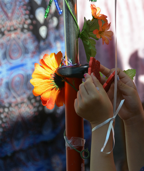close up of hands decorating a scooter with flowers and foam shapes