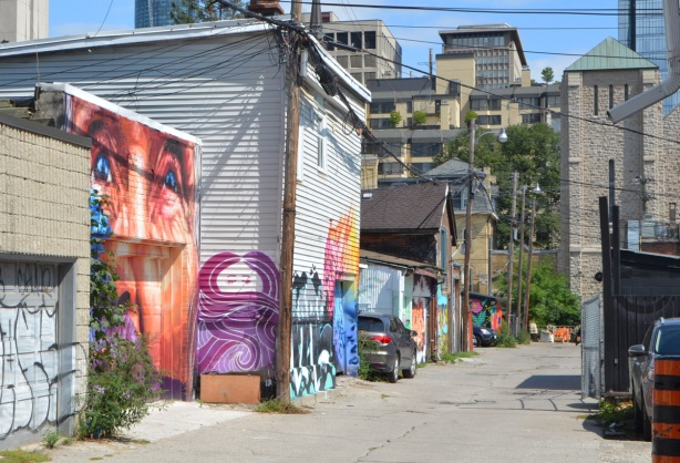 laneway in toronto with some garages with murals on them, tall buildings in background, utility poles and wires,