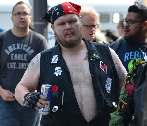 man in black and red bandana, black vest open to reveal bare chest, tattoo above his heart, black glove, carrying a can of red bull