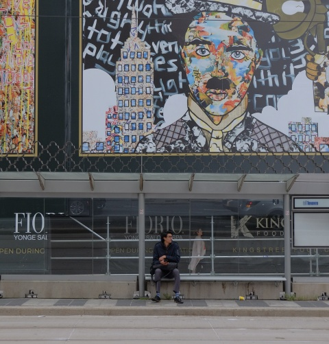 a man sits on a bench at a bus shelter on St. Clair, with a large collage picture of Charlie Chaplin behind him, created by Daniel Mazzone
