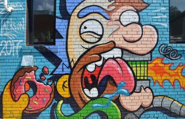 Simpsons parody mural by Jackson in a lane, man eating a donut and drinking Duffs beer.