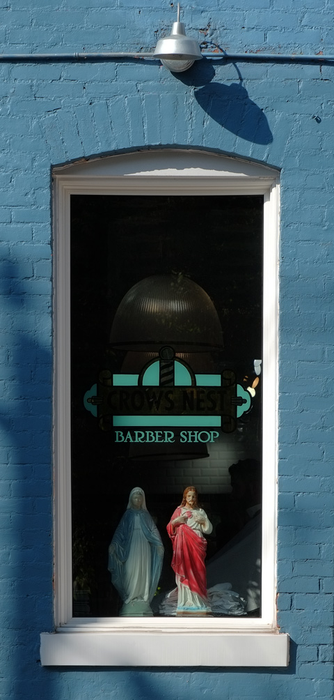 the window of Crows Nest Barber with a statue of Mary and a statue of Jesus in the window