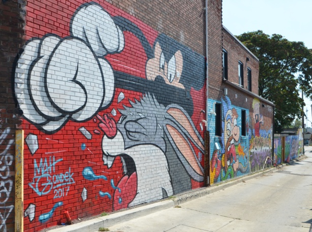 in a popart mural by Matt Gondek and Jackson, in an alley, mickey mouse with his big white gloves is punching bugs bunny whose mouth is wide open and tongue is out