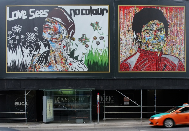 two murals by Daniel Mazzone, one of which is Michael Jackson in his red Thriller jacket, and the other is a woman in a cap blowing dandelions white puffy stuff, other flowers and butterflies too along with the words Love Sees No Colours.
