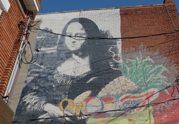 realistic mural of Mona Lisa holding a basket of fruit, high on a wall in Kensington