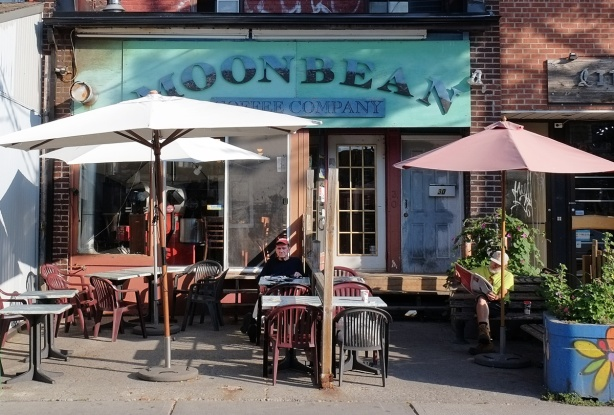 the patio in front of Moonbean coffee shop, with two men sitting at tables
