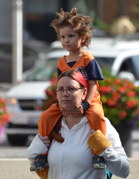 a mother with a child on her shoulders, walking to Fan Expo, child has spiky hair and an orange costume