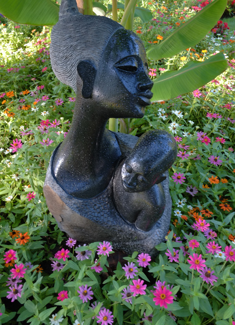 black stone sculpture of a mother holding her son, in a garden, with pink, red and orange flowers around the bottom of the sculpture