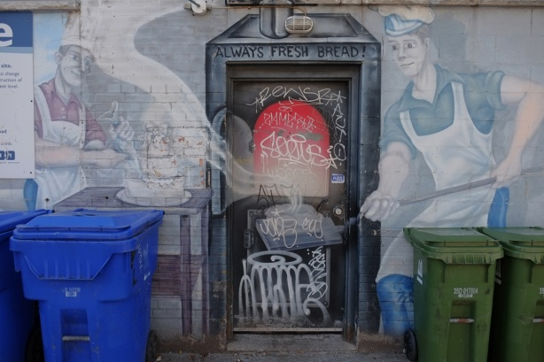 an old and fading mural on the side of an old bakery, showing two bakers, male, baking bread, with chef's hats and white aprons on