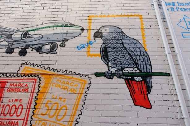 part of a mural in a narrow alley in Kensington by Dave Setrakian, a parrot on a perch and an airplane, some passport stamps