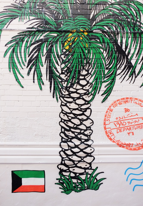 part of a mural in a narrow alley in Kensington by Dave Setrakian, a parrot on a perch and an airplane, a palm tree and a flag