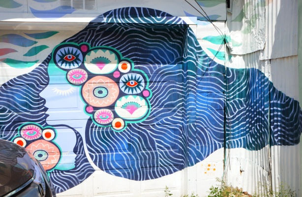 a mural on a garage door of a pale blue woman in profile, with long flowing dark blue hair, symbols and concentric designs in her hair around her face