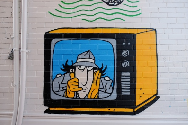 part of a mural in a narrow alley in Kensington by Dave Setrakian, a parrot on a perch and an airplane, a television set showing Ispector Gadget, a cartoon character from a 1990's kids program