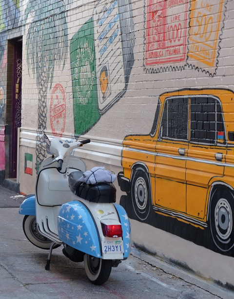 part of a mural in a narrow alley in Kensington by Dave Setrakian, a parrot on a perch and an airplane, a blue and white scooter, motorbike, is parked beside the mural