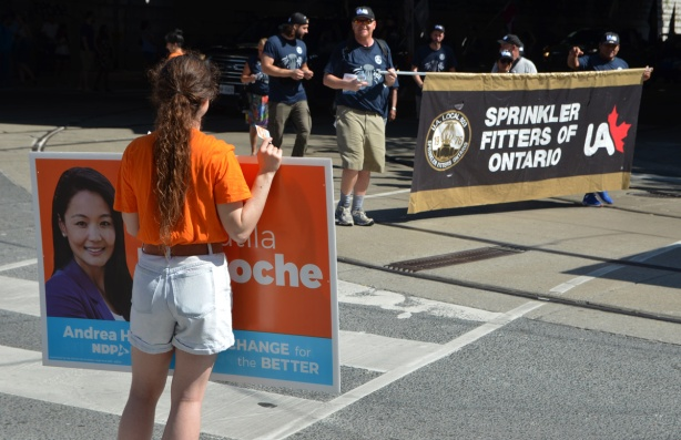labour Day parade on Queen St West, a young woman holds an orange NDP sign for the local Parkdale MPP Bhutial Krapoche, as members of the Sprinkler Fitters of Ontario Union come around the corner from Queen West to Dufferin