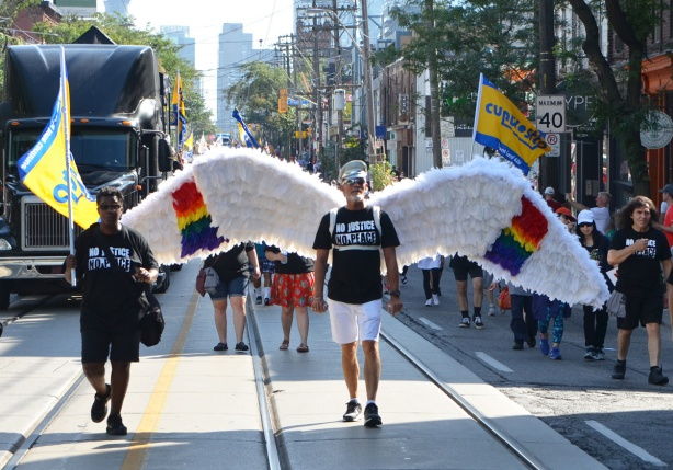 labour Day parade on Queen St West, a man walks with large white wings, about 8 feet across (2.5 metres), he's wearing a black T-shirt with white words that say No Justice No Peace