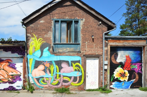 old two storey brick building in a lane with upper window and lower single door. Door has a street art piece on it as does whole lower level, a garage on either side of it each with the door covered in a new mural