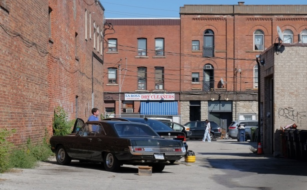 man stands beside on older car in a parking lot surrounded by old brick buildings