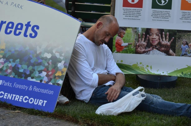 a man has fallen asleep on the grass beside the OPen Streets Park sign,