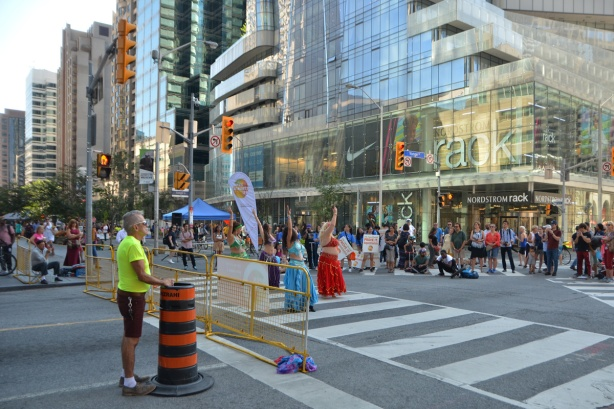 the intersection of Yonge and Bloor at Open Streets, belly dancers performing for an audience, Nordstroms Rack store in the background