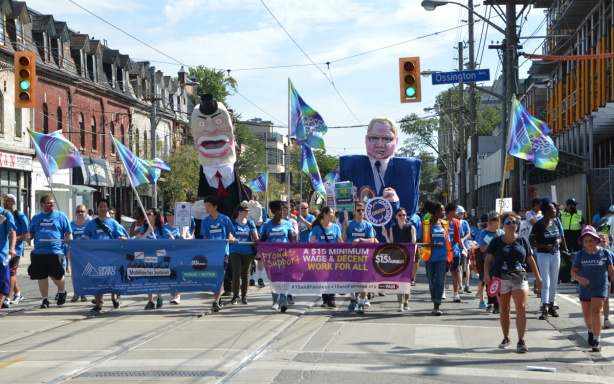OPSEU banners and people in Labour Day parade, inclusing two with large oversized, tall, effigies of Doug Ford and John Tory