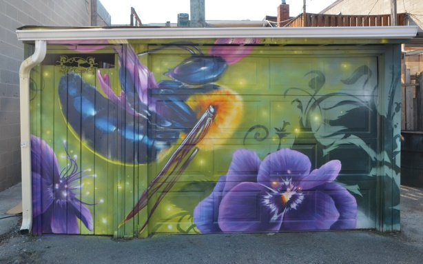 garage door and sides covered with a mural, a purple pansy, an insect with shiny blue body and narrow wings,