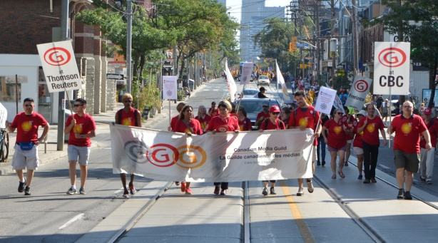 labour Day parade on Queen St West, Canadian Media guild members walk with their banner, wearing red t-shirts