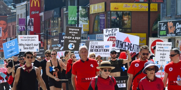 people wearing red T-shirts and carrying signs, walking in a walk to raise funds and awareness for AIDS, on Yonge Street.