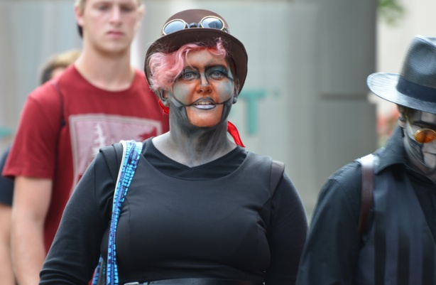 a woman in costume, black top, har, and face paint,