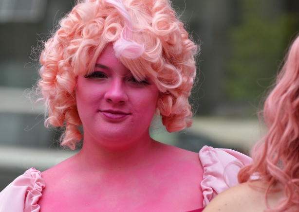 a woman in pale pink wig and totally covered face with pink paint