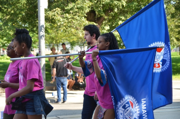 labour Day parade on Queen St West, young people in pink t-shirts carry blue flags for a union,