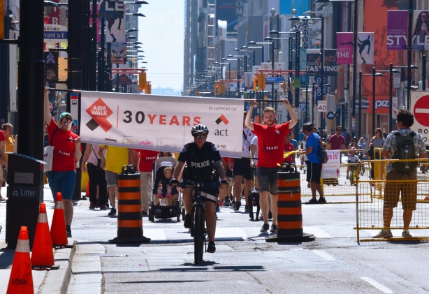 a policeman on a bike leads an AIDS walk up Yonge Street, people holding a banner follow him and then many people wearing red T-shirts