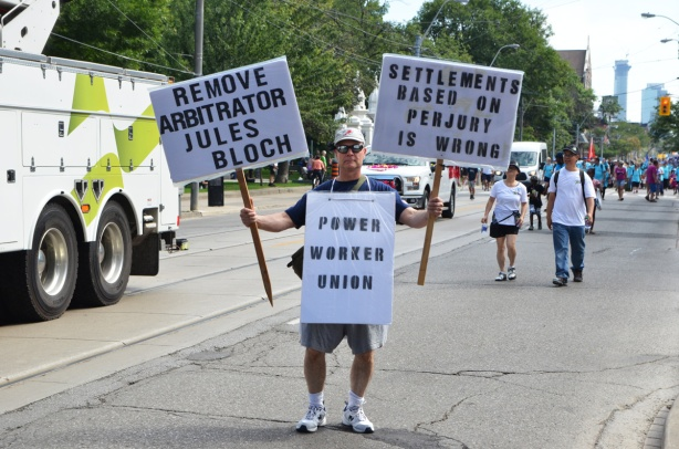 Power Workers union protest signs, held by one man